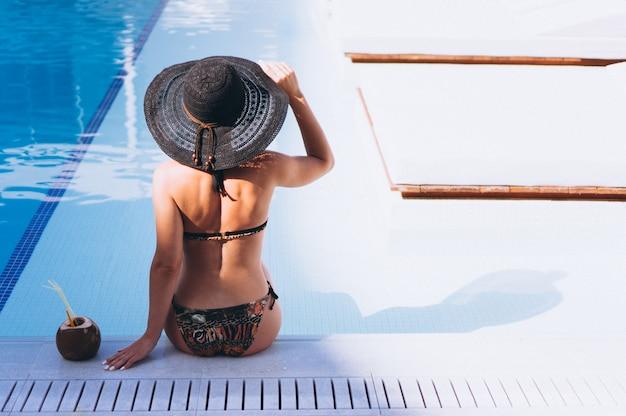Donna in bikini che beve latte di cocco in piscina