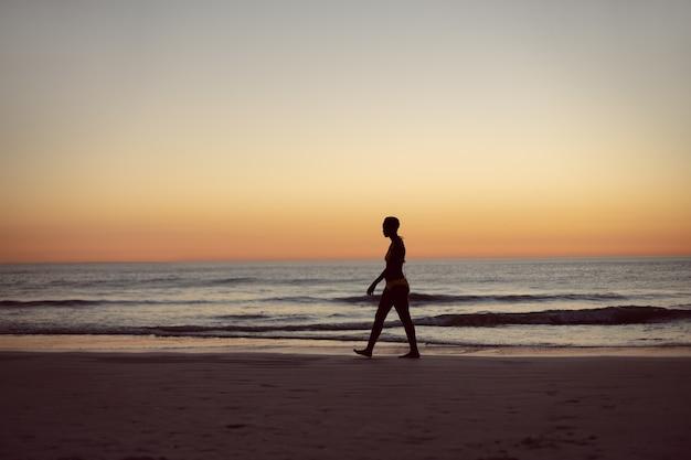 Donna in bikini che cammina sulla spiaggia
