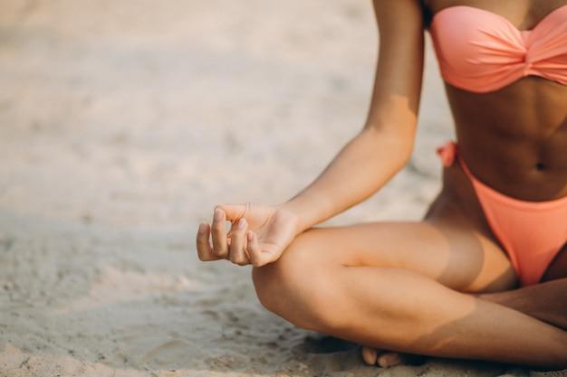 Donna in bikini che praticano yoga in spiaggia