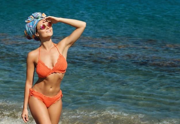 Donna in bikini e occhiali da sole la spiaggia