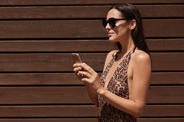 Donna in bikini e occhiali da sole neri che tengono smart phone nelle mani, guardando in lontananza, in posa isolato su uno spazio di legno marrone