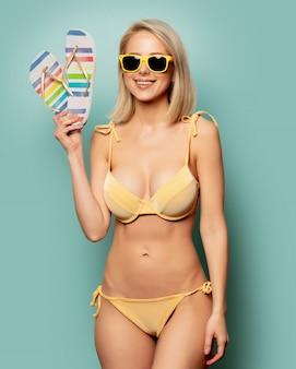 Donna in bikini giallo e occhiali da sole con infradito