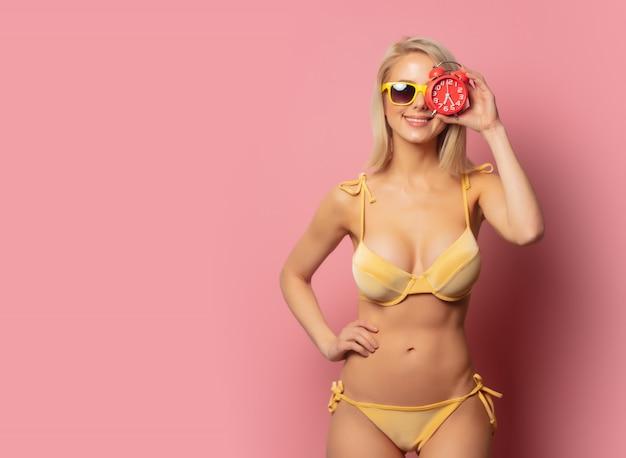 Donna in bikini giallo e occhiali da sole con sveglia