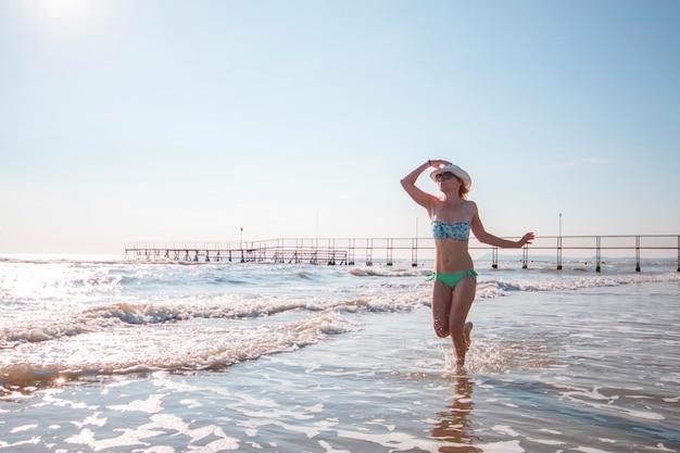 Donna in bikini in esecuzione sulla riva