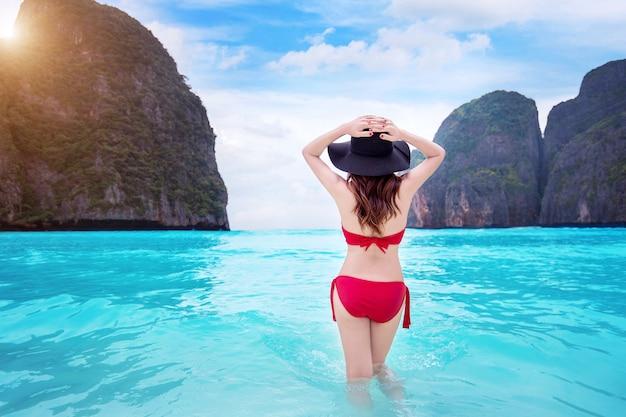 Donna in bikini rosso in spiaggia tropicale.