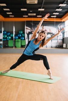 Donna in buona salute che allunga il suo braccio durante l'esercizio
