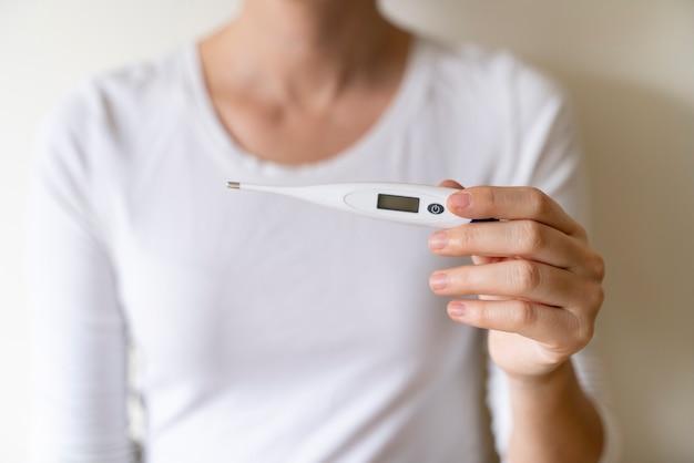 Donna in buona salute che misura con una febbre alta del termometro digitale. mantenere il controllo dei livelli di rischio di alta temperatura nel nostro corpo durante la crisi virale pandemica covid 19. infermiera irriconoscibile.