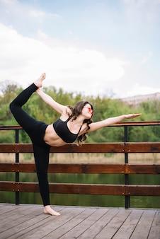 Donna in buona salute che tiene la sua gamba e che equilibra sulla superficie di legno