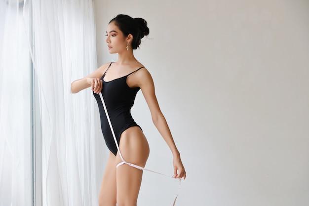 Donna in buona salute ed esile che prende le misure del suo corpo
