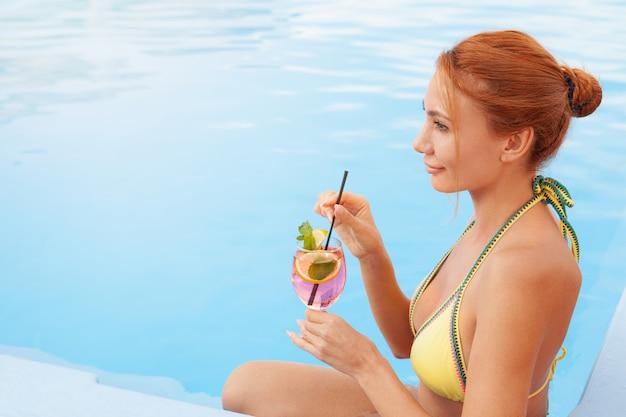 Donna in buona salute felice che si rilassa al bordo della piscina dell'hotel