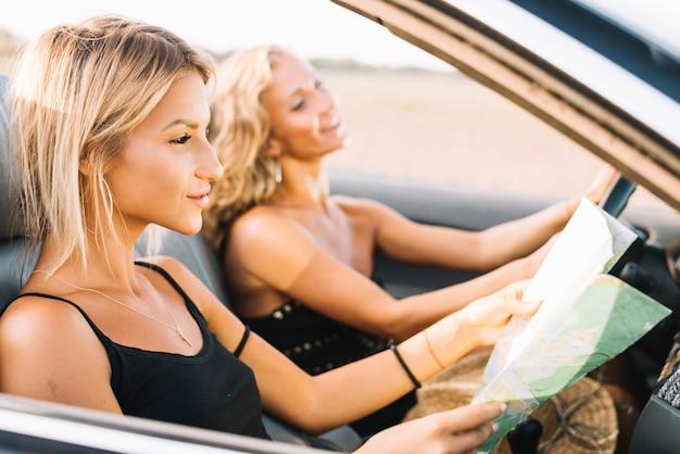 Donna in cabriolet guardando la mappa