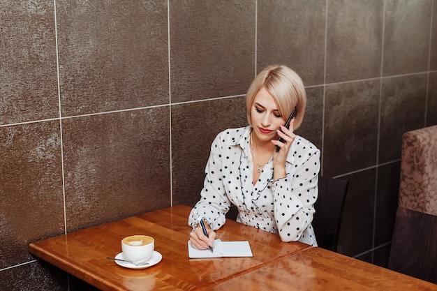Donna in caffè che parla sul telefono e che scrive in taccuino