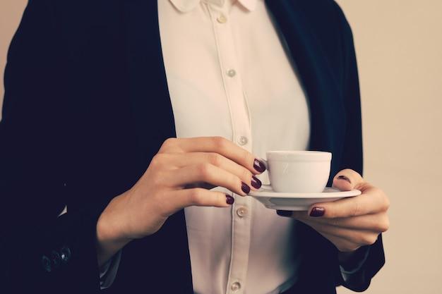 Donna in camicetta bianca e giacca nera in possesso di una tazza di caffè in mano