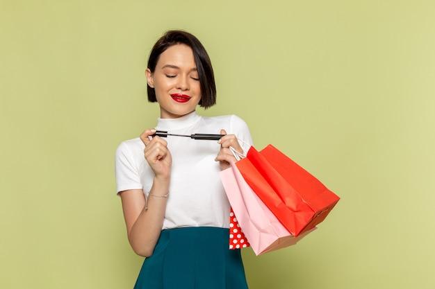 Donna in camicetta bianca e gonna verde che tiene i pacchetti della spesa e mascara
