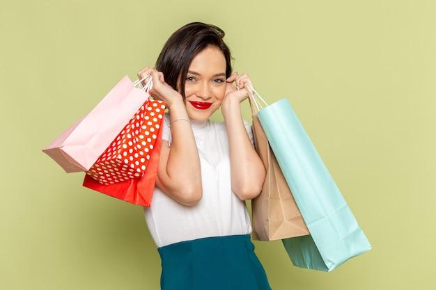 Donna in camicetta bianca e gonna verde che tiene i pacchetti della spesa e sorridente
