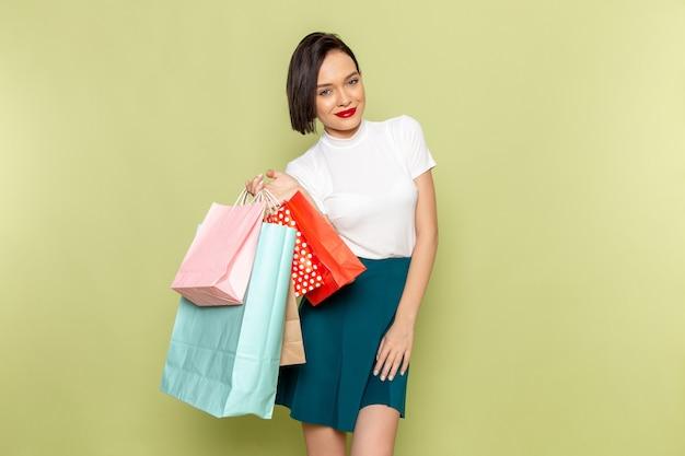 Donna in camicetta bianca e gonna verde che tiene i pacchetti della spesa