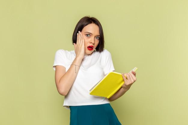 Donna in camicetta bianca e gonna verde che tiene libro giallo e lettura