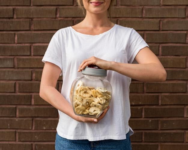 Donna in camicia bianca che tiene fette essiccate di banane