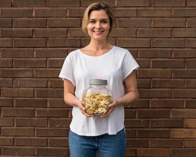 Donna in camicia bianca che tiene le banane essiccate in un barattolo