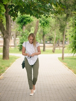 Donna in camicia bianca e pantaloni verdi con gli occhiali da sole in mano camminando per il vicolo del parco.