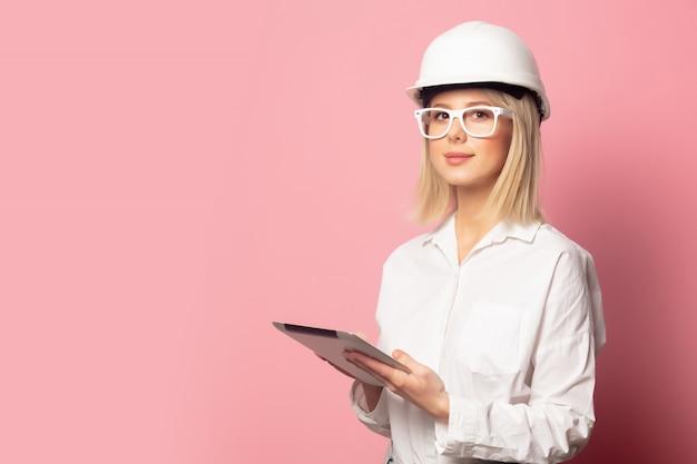 Donna in camicia bianca, occhiali e casco con tavoletta
