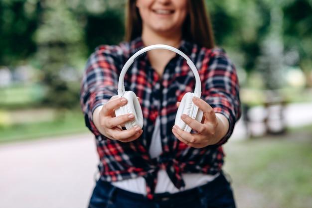 Donna in camicia colorata che tiene le cuffie senza fili, all'aperto