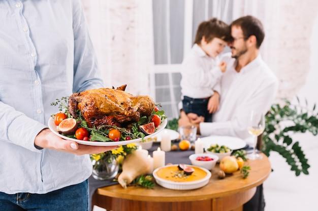 Donna in camicia in piedi con pollo al forno