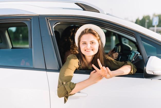 Donna in cappello appeso fuori dal finestrino della macchina