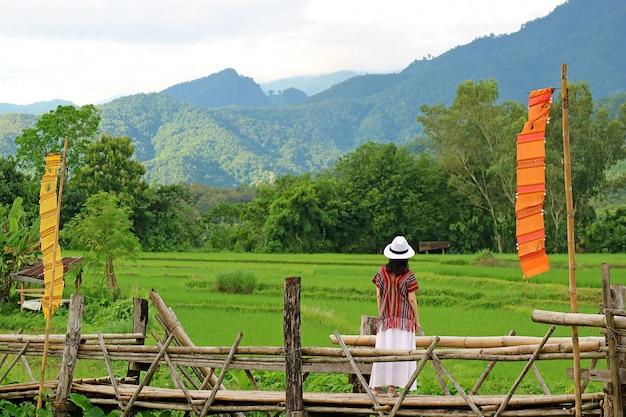 Donna in cappello bianco che esamina la risaia verde vibrante da un ponte di bambù