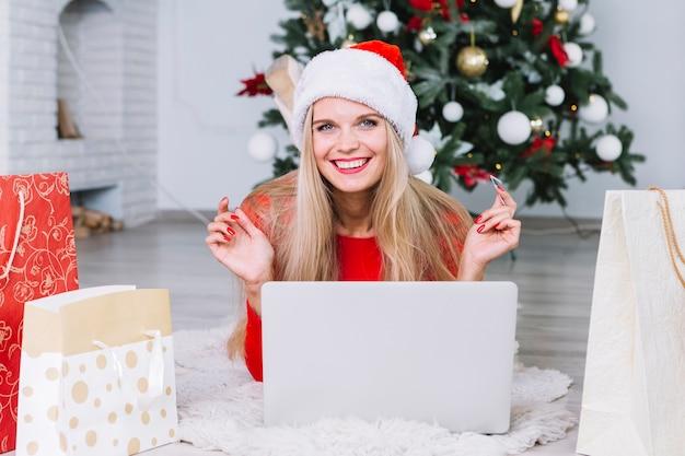Donna in cappello della santa che si trova con il laptop