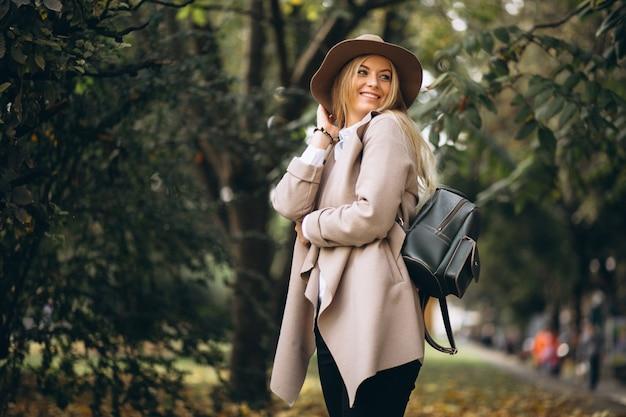 Donna in cappello e cappotto nel parco