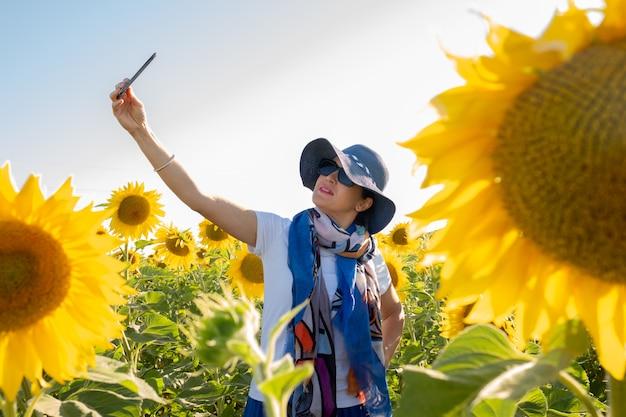 Donna in cappello facendo un selfie in un campo di girasoli
