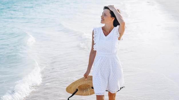 Donna in cappello sulla costa dell'oceano indiano