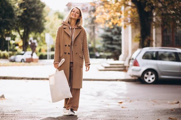 Donna in cappotto beige con la borsa della spesa in strada