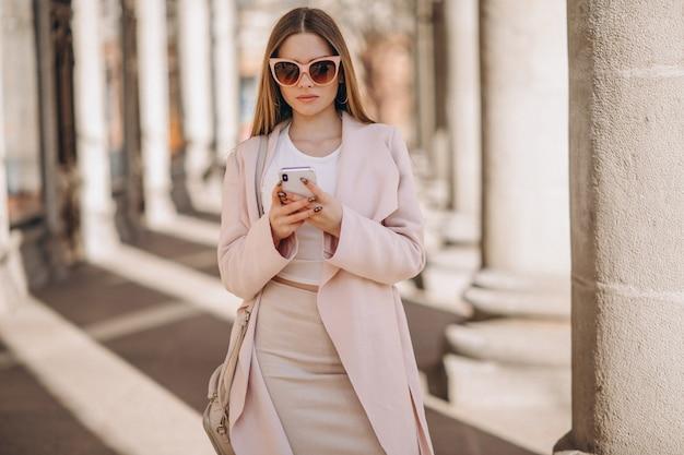 Donna in cappotto camminando per la strada e parlando al telefono