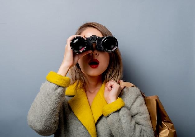 Donna in cappotto con borsa della spesa e binocolo