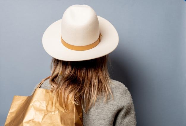 Donna in cappotto con la borsa della spesa