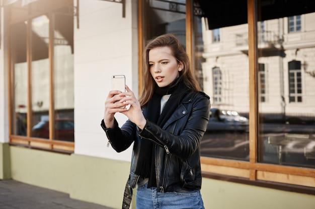 Donna in cappotto di pelle alla moda che tiene smartphone mentre si scatta foto di paesaggi o band che suona in strada