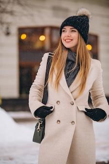 Donna in cappotto in piedi fuori dal caffè in una strada d'inverno