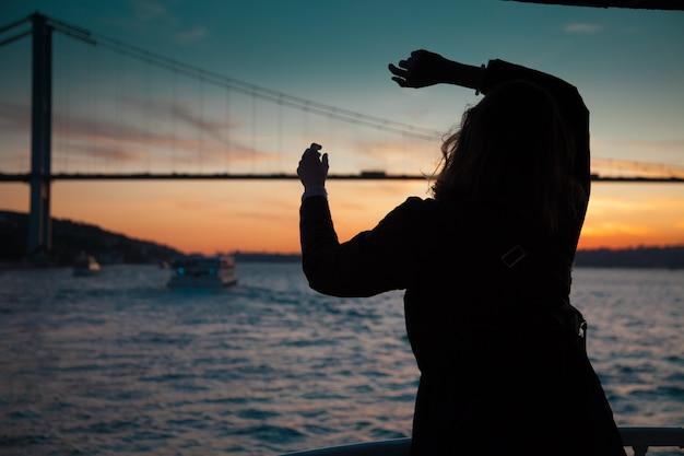 Donna in cappotto scuro in piedi con le mani in alto sul ponte di osservazione nel traghetto