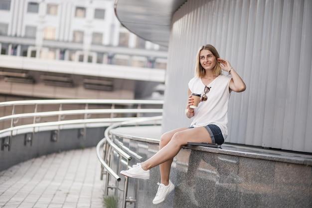 Donna in città con caffè, estate e tempo soleggiato.
