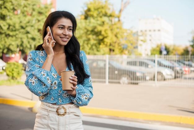 Donna in città con telefono e caffè