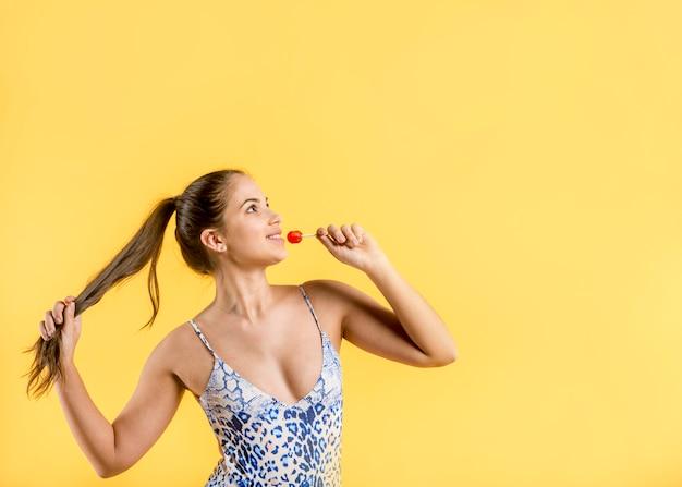 Donna in costume da bagno blu in piedi e tenendo la lecca-lecca
