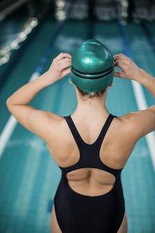 Donna in costume da bagno che regola i suoi occhiali di protezione in piscina