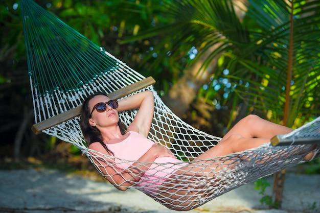 Donna in costume da bagno che si rilassa sull'amaca che prende il sole in vacanza