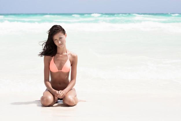 Donna in costume da bagno che si siede sulla spiaggia