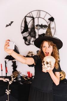 Donna in costume della strega che fa selfie con il cranio