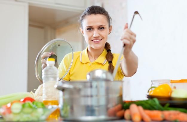 Donna in cucina gialla con mestolo in casseruola