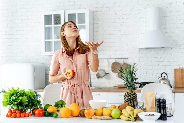 Donna in cucina pronta a preparare il pasto con frutta e verdura.