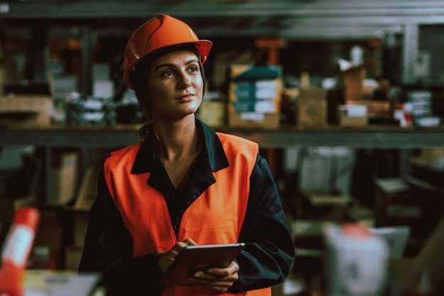 Donna in elmetto protettivo che utilizza la compressa di digital nel magazzino